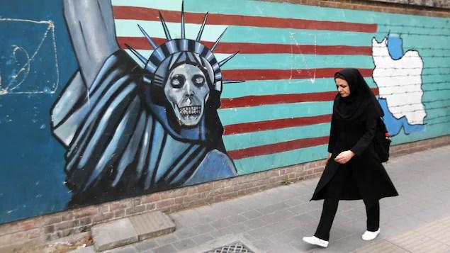 Une femme marche devant un mur de l'ex-ambassade américaine de Téhéran.