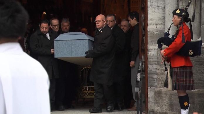 The coffin is moved out of the church by porters.