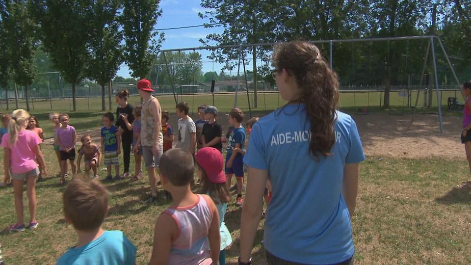 Un instructor da vuelta a un grupo de niños en un parque.