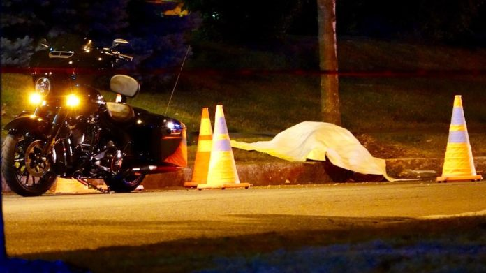 A canvas covers a body near a motorcycle.