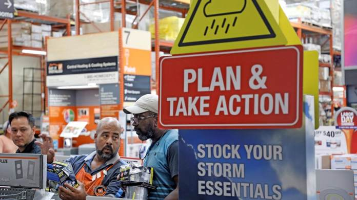 An information board invites customers to a hardware store to prepare for the hurricane.
