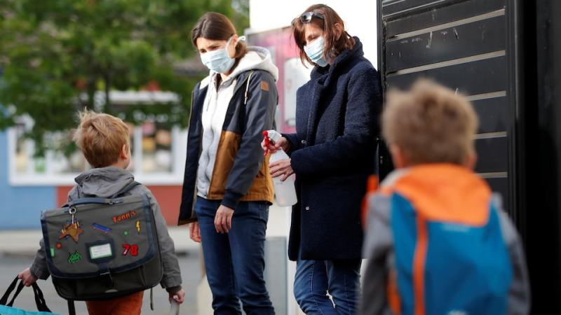 Two female teachers wearing face masks are outside a school and two young boys walk towards them with their school bags.  One of the two women has a bottle of disinfectant in her hand.