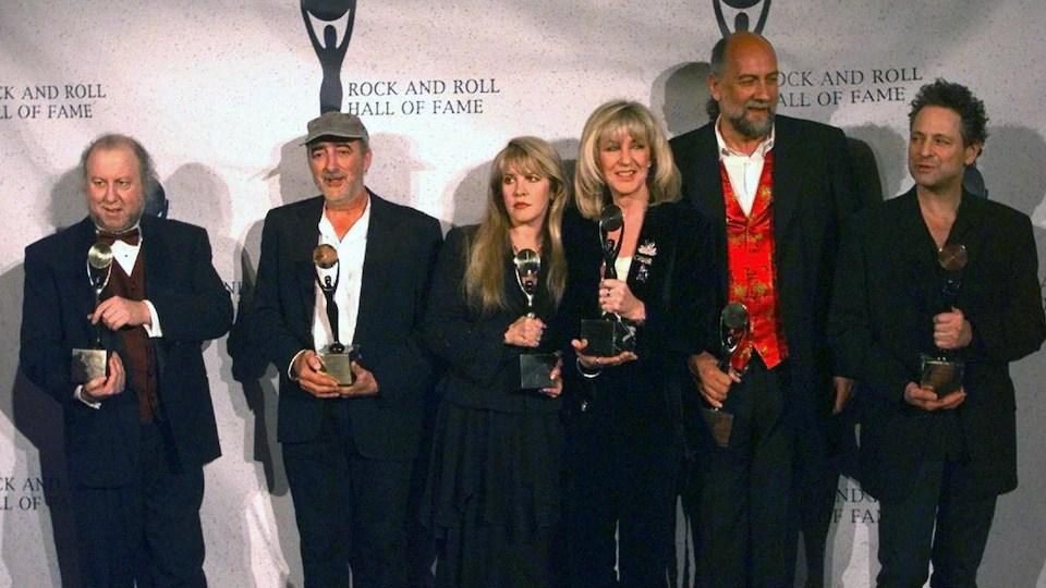Les six membres du groupe tiennent chacun un trophée dans leurs mains.
