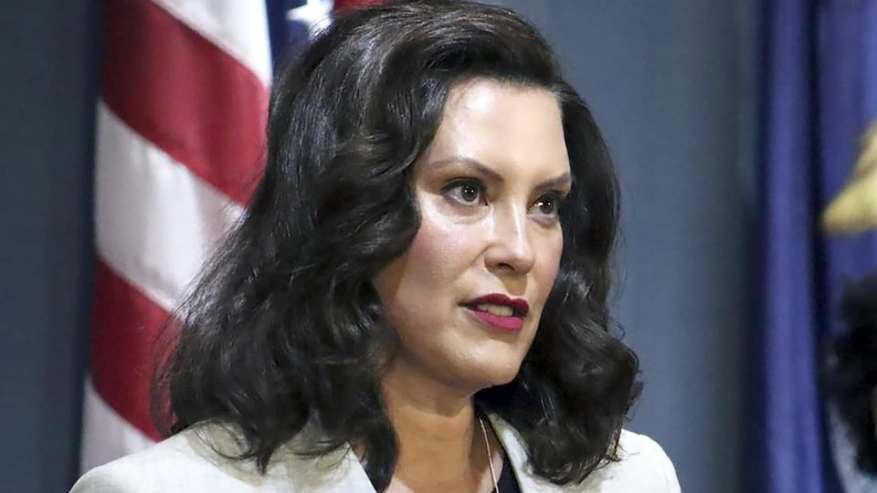 Gretchen Whitmer, sidelined, looking at people she's talking to, in front of an American flag