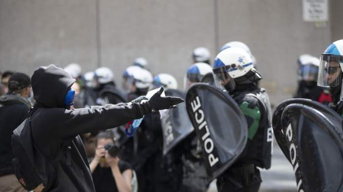 Un manifestante enmascarado se enfrenta a agentes de policía protegidos por sus cascos, viseras y escudos.