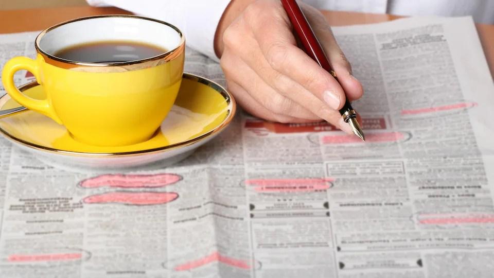 Una persona revisa los clasificados en un periódico en busca de trabajo.