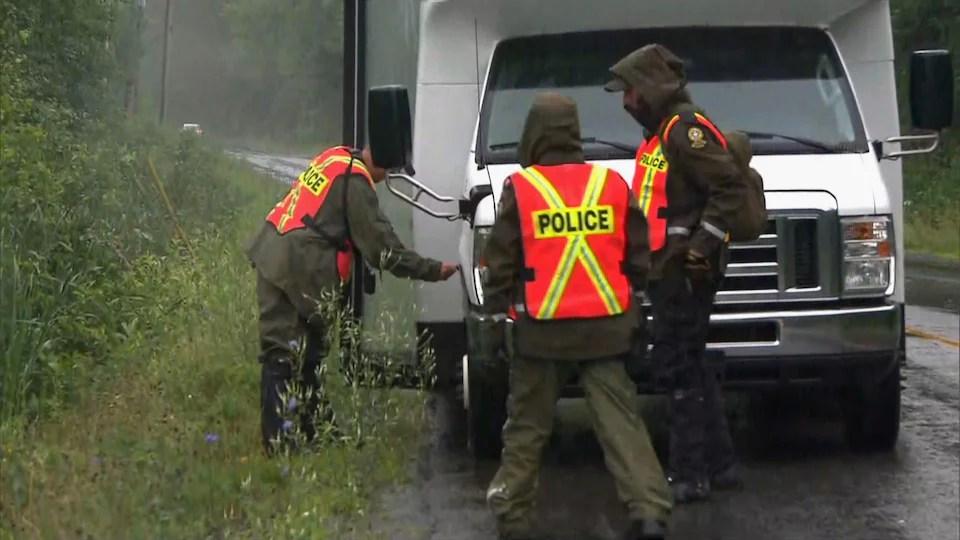 Trois policiers en habit imperméables dehors, sous la pluie, sur une route bordée d'arbres, à côté d'un petit autobus.