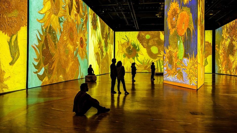 Des spectateurs dans une salle où sont projetées des toiles du peintre Vincent Van Gogh.