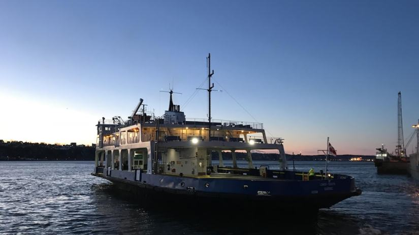 A ferry leaving from Quebec to Lévis on the river at dawn.