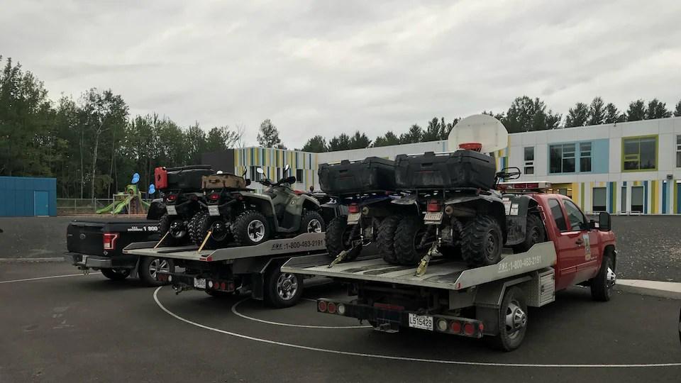 Des véhicules stationnés, avec des VTT dans des remorques, aux couleurs du ministère de la Faune, dans un stationnement d'école, le jour