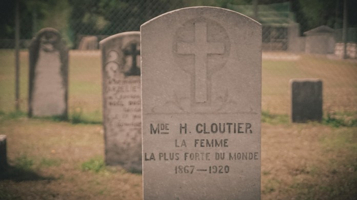"""A tombstone on which one can read: """"Mrs. H. Cloutier, the strongest woman in the world""""."""