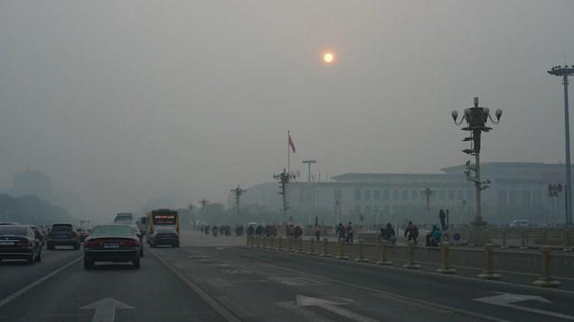 Une rue de Pékin sous le smog et un soleil obscurci