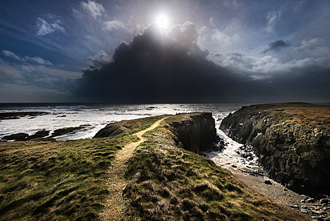 A day of mixed weather, brilliant sunshine and violent hail showers over the Irish Sea on the West coast of Anglesey, Wales, United Kingdom