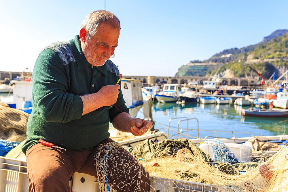 Stock photo of Fisherman mending nets at Cetara harbour