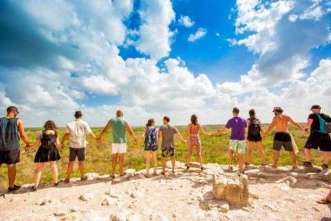 Stock Adventure Photo: Group of people hold hands at the summit of Nohoch Mul Pyramid in the Ancient Mayan City of Coba, outside Tulum, Mexico, North America