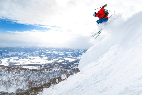 A male skier is jumping in the air onto a slope with deep powder snow in the ski resort Niseko United on the Japanese island of Hokkaido