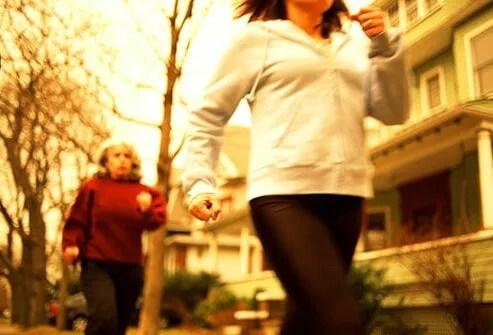 Two women power walking through their neighborhood.