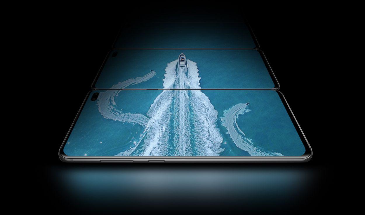 Vista ligeramente angulada, desde el lateral de los botones de volumen y Bixby, de tres teléfonos Galaxy S10 plus en modo horizontal colocados uno tras otro. Las tres pantallas, con una imagen aérea de un barco en el agua y dos personas practicando esquí acuático, muestran la amplitud de la pantalla Infinity-O.