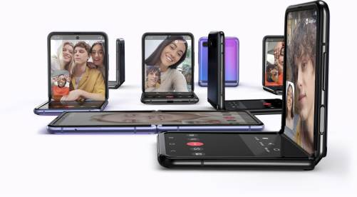 Multiple Galaxy Z Flip phones, some folded at right angles and others unfolded. All have the Google Duo interface onscreen for high-definition video chatting across different OS