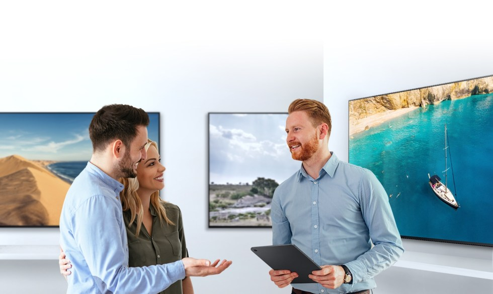 For buying a new TV, a man and woman are talking with a male sales representative about TV features in a TV show room.