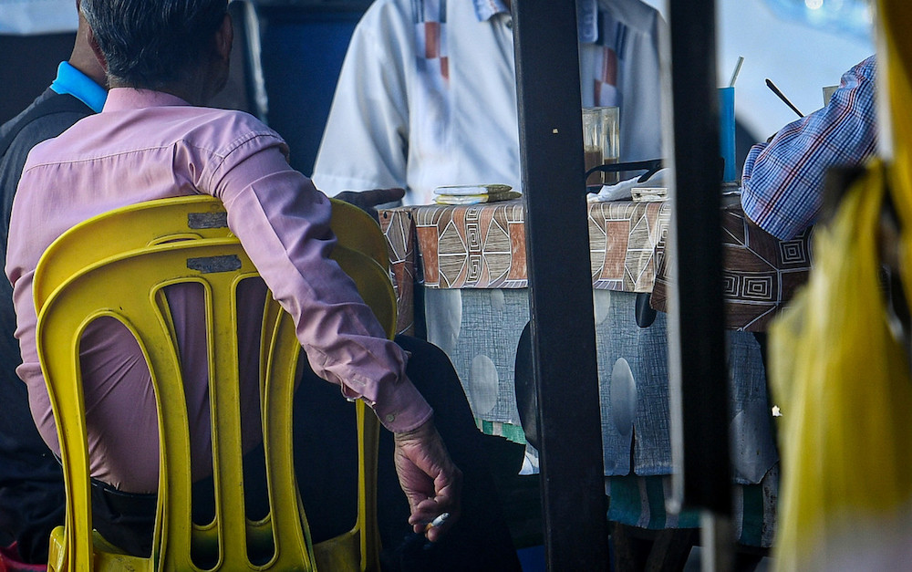 A man attempts to conceal his cigarette as health officers approach his table in Kuala Lumpur yesterday, 1 January.
