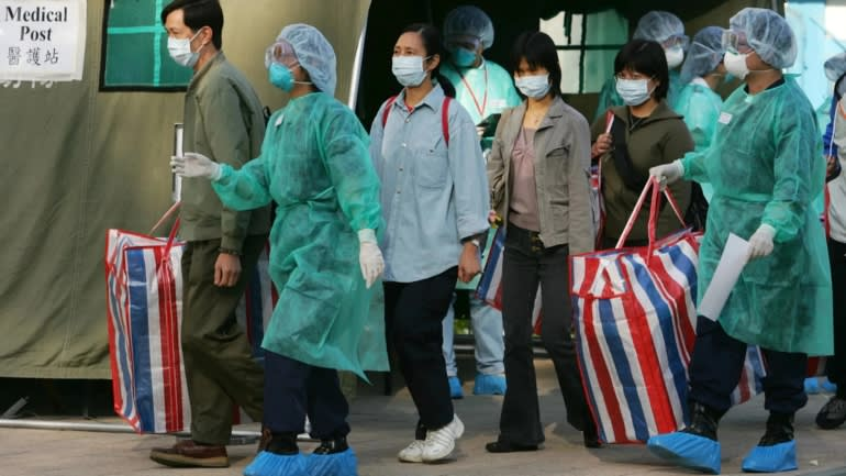 Health workers evacuating 'infected patients' from a building during a SARS outbreak drill in Hong Kong in 2004.