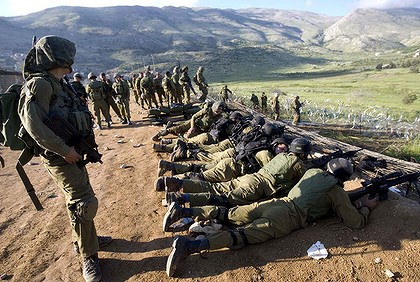 Israeli Soldiers at trampled fence in the Golan