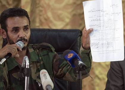 "Ajmi al-Atiri, commander of the Zintan brigade that arrestedf Seif al-Islam, the detained son of slain leader Moamer Kadhafi, shows a document during a press conference in the Libyan city of Zintan on June 9, 2012. Libya has arrested a female Australian lawyer from the International Criminal Court for trying to pass ""dangerous"" documents to Seif al-Islam, the ICC's Libyan representative said the same day."