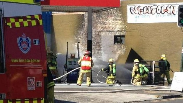 Firefighters standby as gas bottles in a service station are doused with water to prevent an explosion on King Street.