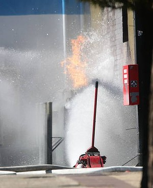 Gas bottles in a service station are doused with water to prevent an explosion on King Street.