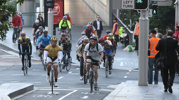 Cyclist ride into Sydney in the morning rush, using the bike lane in King Street.