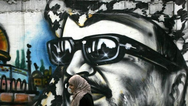 A woman walks past a mural of former Palestinian leader Yasser Arafat