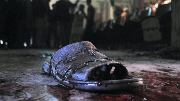 A blood-stained shoe of a victim lies on the ground at the site of a grenade attack on a crowded movie theatre that killed and wounded many people in Peshawar, Pakistan.