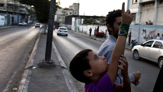 A Palestinian boy points up to the sky as he spots two Israeli drones.
