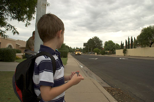 Connor watching the bus approach the bus stop.