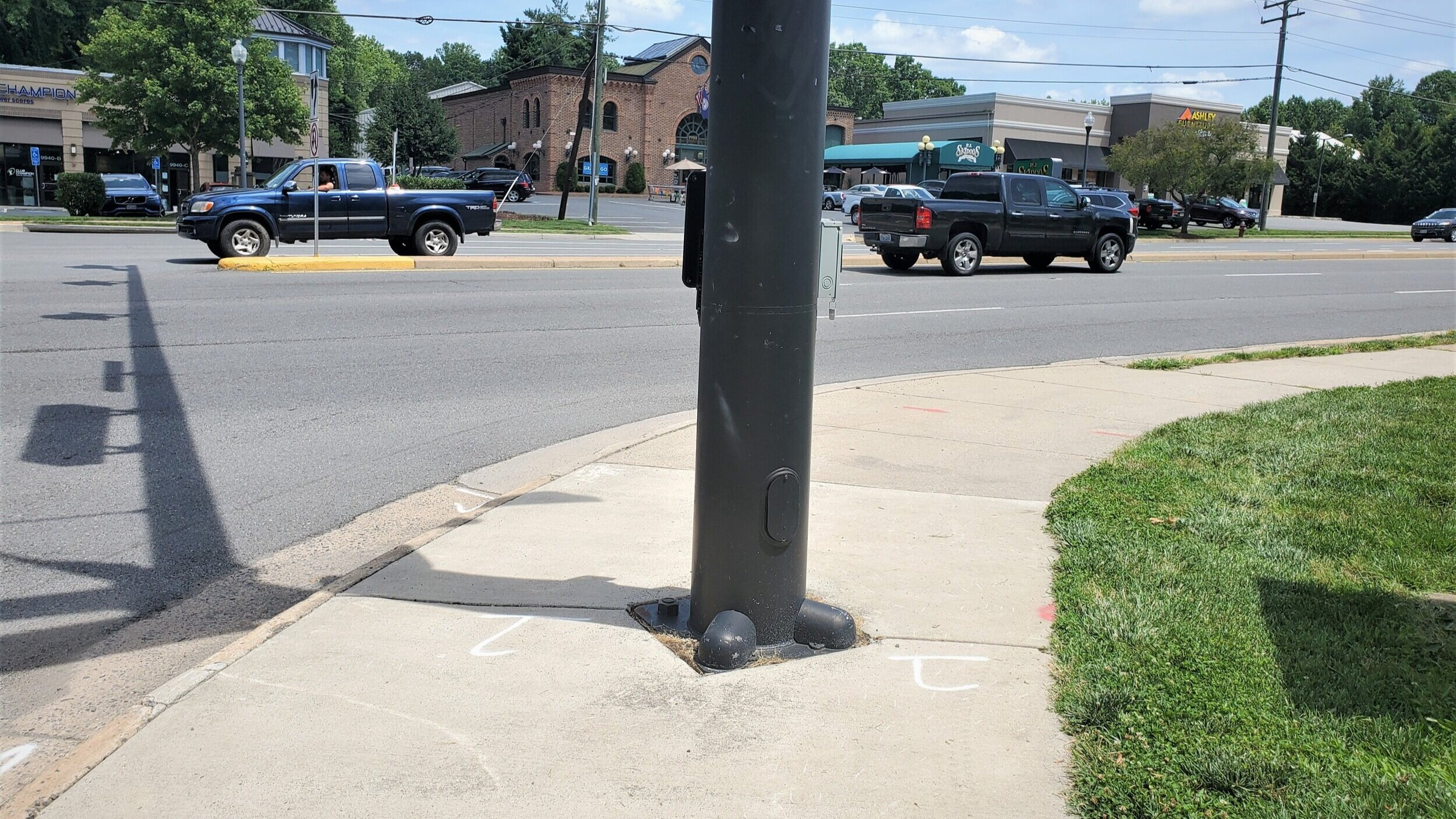 """A traffic light pole with a """"beg button"""" for crossing is placed in the middle of the sidewalk."""