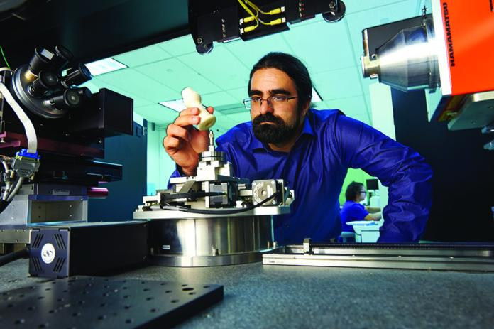 A UConn Engineering researcher works with a 3-D printer to produce an instrument component. (UConn Today)