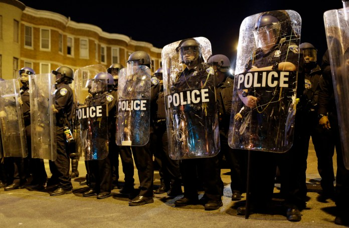 Police stand in formation as a curfew approaches, Tuesday, April 28, 2015, in Baltimore, a day after unrest that occurred following Freddie Gray's funeral. (Patrick Semansky/AP)