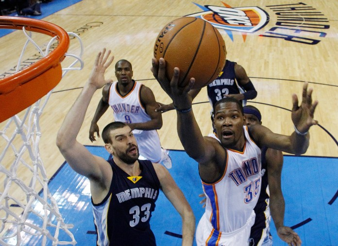 In this Feb. 11, 2015, file photo, Oklahoma City Thunder forward Kevin Durant (35) shoots in front of Memphis Grizzlies center Marc Gasol (33) during the first quarter of an NBA basketball game in Oklahoma City. (Sue Ogrocki/AP)