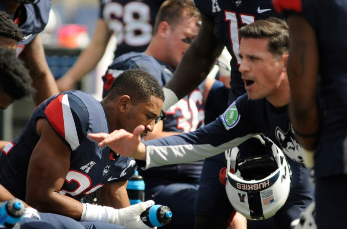 UConn football safety Andrew Adams sits on the sideline as head coach Bob Diaco talks with the defense during the Huskies' game against Navy at Pratt & Whitney Stadium at Rentscher Field on Saturday, Sept. 26, 2015. UConn lost 28-18. (Bailey Wright/The Daily Campus)