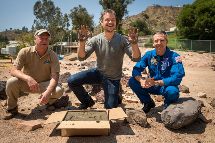 """Actor Matt Damon, who stars as NASA Astronaut Mark Watney in """"The Martian,"""" smiles after making hand prints in cement at the Jet Propulsion Laboratory (JPL) Mars Yard while Mars Science Lab Project Manager Jim Erickson and NASA Astronoaut Drew Feustel look on. The movie is based on NASA data and realistically portrays what life would be like on Mars. (Bill Ingalls NASA/Flickr)."""