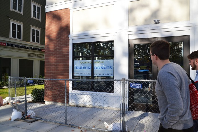 """People walk past a coming soon sign on the future Dunkin' Donuts storefront in Storrs Center.Dunkin' Donuts will open a new location in Storrs Center by 2016 to """"alleviate the pressure"""" on the Student Union location, said Dunkin Donuts' franchisee, Derek Pacheco. (Amar Batra/The Daily Campus)"""