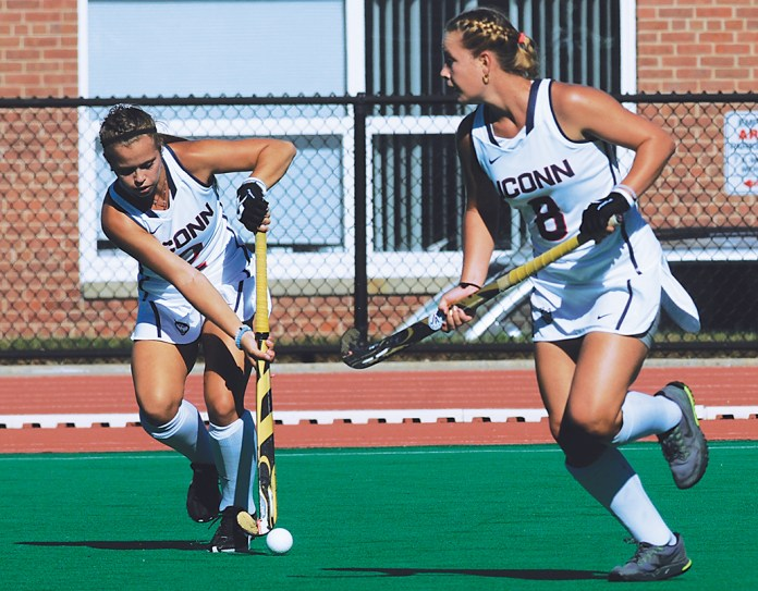 UConn junior forward Monica Fleming (left) passes the ball past sophomore forward Casey Umstead during a UConn field hockey game at the Sherman Family Sports Complex in Storrs, Connecticut. (Bailey Wright/The Daily Campus)