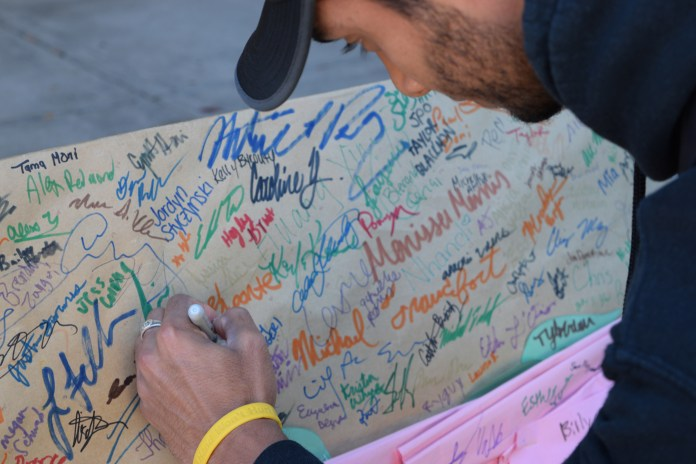 A student signs a UConnPirg petition Subway to end its use of products made with livestock raised on antibiotics on Monday, Oct. 13, 2015. (Grant Zito/The Daily Campus)