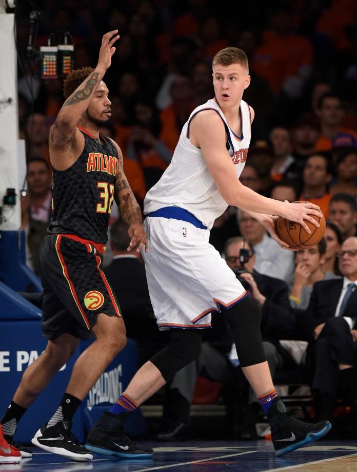 New York Knicks forward Kristaps Porzingis (6) looks to pass the ball around Atlanta Hawks forward Mike Scott (32) during the second half of an NBA basketball game on Thursday, Oct. 29, 2015, in New York. The Hawks won 112-101. (Kathy Kmonicek/AP)