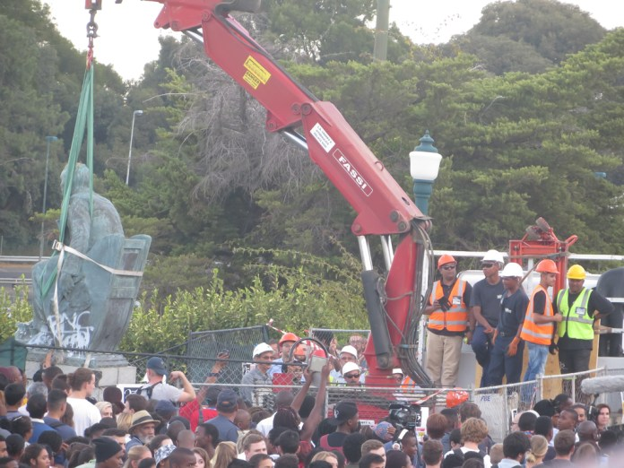 Students gather as a statue of Cecil Rhodes is removed from the University of Cape Town campus in Cape Town, South Africa in April 2015. (tony4carr/Flickr)