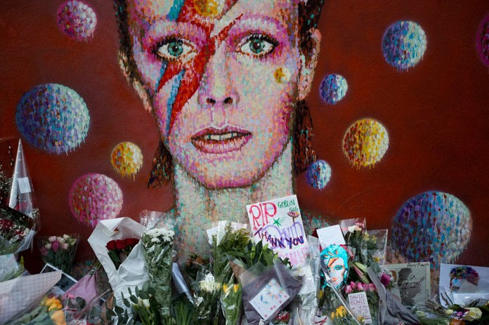 Tributes lie beneath a mural of British singer  David  Bowie by artist Jimmy C in Brixton, south London, Tuesday, Jan. 12, 2016. Bowie , the other-worldly musician who broke pop and rock boundaries with his creative musicianship, nonconformity, striking visuals and a genre-spanning persona he christened Ziggy Stardust, died of cancer Sunday aged 69. He was born in Brixton. (AP Photo/Matt Dunham)