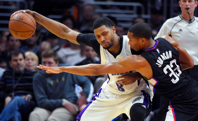 Los Angeles Clippers forward Wesley Johnson, right, reaches for the ball held by Sacramento Kings forward Rudy Gay during the first half of an NBA basketball game, Saturday, Jan. 16, 2016, in Los Angeles. (Mark J. Terrill/AP)