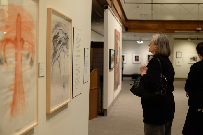 A woman looks at a piece of art at the new exhibit at The William Benton Museum in Storrs, Connecticut on Jan. 21, 2016. (Amar Batra/The Daily Campus)