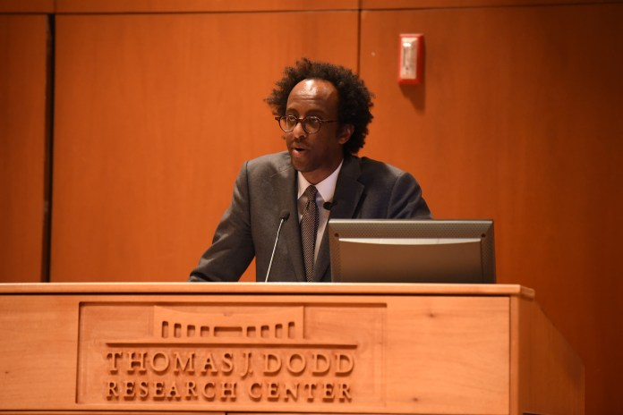 Dinaw Mengestu gives the lecture in Konover Tuesday afternoon about his personal experience on novel creating. (Zhelun Lang/The Daily Campus)